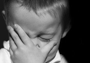 手で顔をおおって泣いている子供の写真