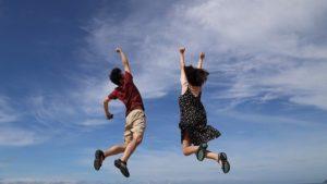 男女2人が青空の下で喜んでジャンプしている