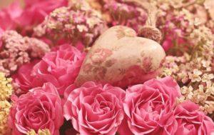ピンクのバラたちの中にハートのオブジェのある写真